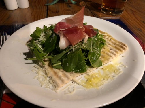 A fresh salad served on top of flatbread with prosciutto